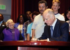 Gov. Jerry Brown signs a bill in September to raise the state's minimum wage. Photo: Nick Ut, Associated Press