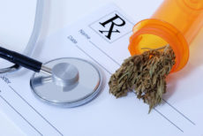 12566026 - cannabis bud sitting on a prescription pad, near a stethoscope
