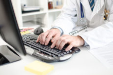 33919068 - doctor typing on a computer keyboard at office