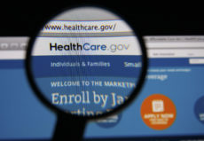 34778261 - lisbon - january 14, 2014: photo of healthcare.gov homepage on a monitor screen through a magnifying glass.