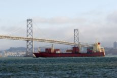 528661 - crgo ship under bay bridge with san francisco on background