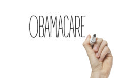 30216439 - hand writing obamacare on a white board