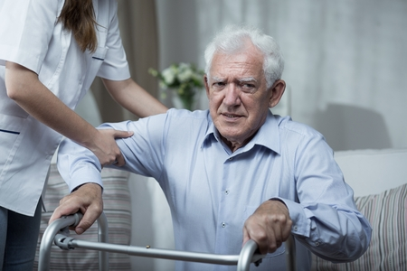 43066070 - physiotherapist helping disabled senior man with standing